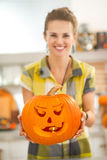 Closeup on housewife showing pumpkin Jack-O-Lantern with candle Royalty Free Stock Images