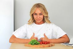 Closeup on housewife showing thumbs up in front of a plate of vegetables, she approves of vegan food stock photo