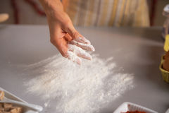 Closeup on housewife sprinkling flour on table Stock Photography