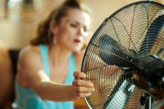 Closeup on housewife using fan suffering from summer heat royalty free stock photo