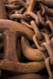 Closeup of huge rusty chain links. Orkneys, Scotland - June 5, 2012: Closeup of heap of huge rusty heavy metal chain links on the pier of the Stromness harbor royalty free stock photo
