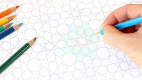 Closeup of human hand drawing, coloring decorative arab tile pattern with geometric stars. Composition with colored stock video