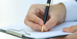 Businessman signs a contract. Holding pen in hand. Royalty Free Stock Photos