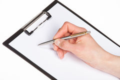 Closeup of a human hand writing with pen on clipboard Stock Photo