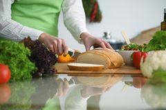 Closeup of human hands cooking in kitchen on the glass table with reflection. Housewife slicing bread.  Stock Image