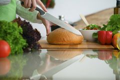 Closeup of human hands cooking in kitchen on the glass table with reflection. Housewife slicing bread.  Stock Photo