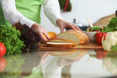 Closeup of human hands cooking in kitchen on the glass table with reflection. Housewife slicing bread Stock Photos