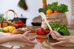Closeup of human hands cooking in kitchen. Women discuss a menu. Healthy meal, vegetarian food and lifestyle concepts.  Royalty Free Stock Image