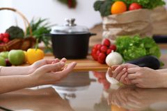 Closeup of human hands cooking in kitchen. Women discuss a menu. Healthy meal, vegetarian food and lifestyle concepts.  Royalty Free Stock Photography