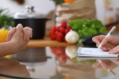 Closeup of human hands cooking in kitchen. Women discuss a menu. Healthy meal, vegetarian food and lifestyle concepts.  Stock Photography