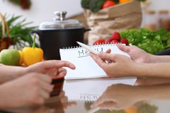 Closeup of human hands cooking in kitchen. Women discuss a menu using block note. Copy space area. Healthy meal. Vegetarian food and lifestyle concepts Royalty Free Stock Photo