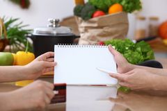 Closeup of human hands cooking in kitchen. Women discuss a menu using block note. Copy space area. Healthy meal. Vegetarian food and lifestyle concepts Royalty Free Stock Images