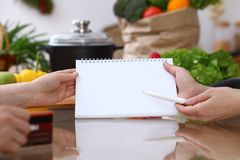 Closeup of human hands cooking in kitchen. Women discuss a menu using block note. Copy space area. Healthy meal. Vegetarian food and lifestyle concepts Royalty Free Stock Image