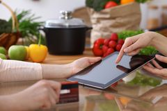 Closeup of human hands cooking in kitchen. Women discuss a menu using tablet computer. Copy space area at touch pad. Healthy meal, vegetarian food and Stock Photography
