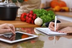Closeup of human hands cooking in kitchen. Women discuss a menu using tablet computer. Copy space area at touch pad. Healthy meal, vegetarian food and Royalty Free Stock Image