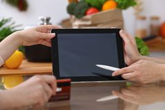 Closeup of human hands cooking in kitchen. Women discuss a menu using tablet computer. Copy space area at touch pad. Healthy meal, vegetarian food and Royalty Free Stock Photos