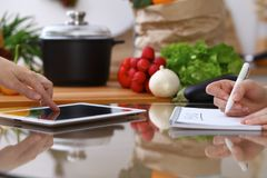 Closeup of human hands cooking in kitchen. Women discuss a menu using tablet computer. Copy space area at touch pad. Healthy meal, vegetarian food and Royalty Free Stock Images