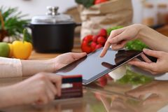 Closeup of human hands cooking in kitchen. Women discuss a menu using tablet computer. Copy space area at touch pad. Healthy meal, vegetarian food and Stock Photo