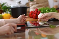 Closeup of human hands cooking in kitchen. Women discuss a menu using tablet computer. Copy space area at touch pad. Healthy meal, vegetarian food and Royalty Free Stock Photo