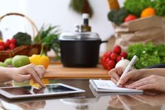 Closeup of human hands cooking in kitchen. Women discuss a menu using tablet computer. Copy space area at touch pad. Healthy meal, vegetarian food and Stock Images