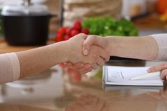 Closeup of human hands cooking in kitchen. Women shaking hands finishing up  discussing a menu. Healthy meal, vegetaria. N food and lifestyle concepts Stock Photo
