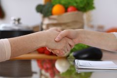 Closeup of human hands cooking in kitchen. Women shaking hands finishing up discussing a menu. Healthy meal, vegetaria royalty free stock images