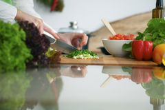 Closeup of human hands cooking vegetables salad in kitchen on the glass  table with reflection. Closeup of human hands cooking vegetables salad in kitchen on the Stock Image