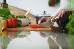 Closeup of human hands cooking vegetables salad in kitchen on the glass  table with reflection. Closeup of human hands cooking vegetables salad in kitchen on the Royalty Free Stock Photo