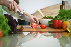 Closeup of human hands cooking vegetables salad in kitchen on the glass  table with reflection. Closeup of human hands cooking vegetables salad in kitchen on the Stock Photos