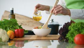 Closeup of human hands cooking vegetables salad in kitchen on the glass  table with reflection. Closeup of human hands cooking vegetables salad in kitchen on the Stock Images