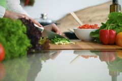 Closeup of human hands cooking vegetables salad in kitchen on the glass  table with reflection. Closeup of human hands cooking vegetables salad in kitchen on the Royalty Free Stock Photography
