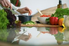 Closeup of human hands cooking vegetables salad in kitchen on the glass  table with reflection. Closeup of human hands cooking vegetables salad in kitchen on the Royalty Free Stock Images
