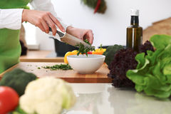 Closeup of human hands cooking vegetables salad in kitchen on the glass  table with reflection Stock Photography