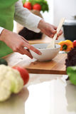 Closeup of human hands cooking vegetables salad in kitchen on the glass  table with reflection Stock Image
