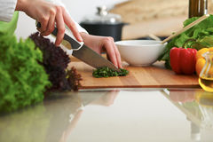 Closeup of human hands cooking vegetables salad in kitchen on the glass  table with reflection Stock Photo