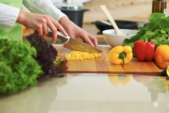 Closeup of human hands cooking vegetables salad in kitchen on the glass  table with reflection Royalty Free Stock Images