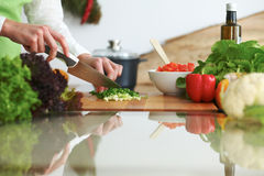 Closeup of human hands cooking vegetables salad in kitchen on the glass  table with reflection Royalty Free Stock Photography