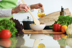 Closeup of human hands cooking vegetables salad in kitchen on the glass  table with reflection Stock Photos