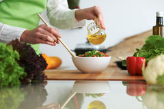 Closeup of human hands cooking vegetables salad in kitchen on the glass  table with reflection Royalty Free Stock Photo