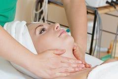 Closeup of human hands massaging a woman's face Stock Photos