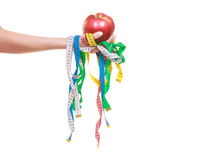 Closeup of human holding apple and tape measures. Royalty Free Stock Photos