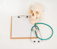 Closeup on human skull stethoscope and clipboard Stock Photo