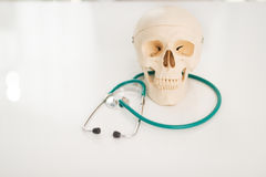 Closeup on human skull and stethoscope Stock Photos