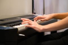 Closeup humans hands playing electronic piano. Favourite classical music. Music classes, learning how to play musical instrument royalty free stock image