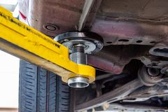 Hydraulic car lift arm holding a vehicle. Closeup of hydraulic car lift arm holding a vehicle royalty free stock images