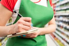 Closeup of hypermarket employee writing in notebook royalty free stock images