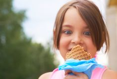 Closeup of ice cream held in hand by cute young girl. Little Caucasian girl eating ice cream in a waffle cone. Closeup of ice cream held in hand by cute young royalty free stock images