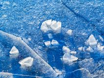 Abstract: Ice and Ice Fragments. Closeup of ice and ice fragments in shades of blue on the surface of a reservoir stock photos
