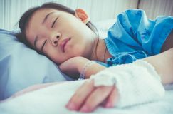 Illness asian child admitted in hospital with saline intravenous. Closeup of illness asian child admitted in hospital with saline intravenous IV on hand. Girl Royalty Free Stock Photos