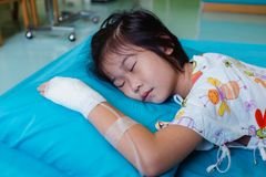 Illness asian child admitted in hospital with saline intravenous on hand. Closeup of illness asian child admitted in hospital with saline intravenous IV on hand royalty free stock image